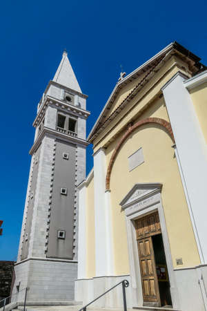 A view on a church and a bell tower from the bottom. The walls of the church are painted yellow, and bell tower's are painted grey. Buildings nicely contrasted with a clear blue sky. 写真素材