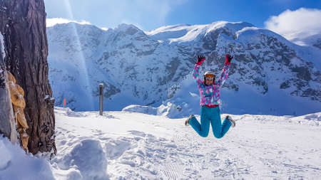 A girl in a snowboarding outfit and a helmet jumping up high. There is a lot of snow all around her. A huge mountain massive in the back. Girl is happy, she enjoys her time. Winter wonderland.