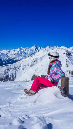 Snowboarder girl sitting on the side of a slope admiring the tall Alps. Slopes are covered with powder snow. Perfect weather for a ride. High alpine snowboarding. Girl wears a helmet for protection