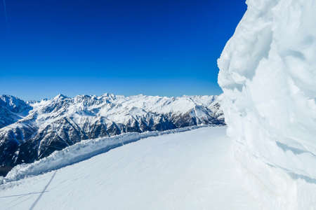 Frozen side of a boulder. Icy wall prevents the skiers from bumping into a rock. Perfectly groomed slope with a view on tall, snow-caped Alps. Sunny day in Heiligenblut, Austria. Banque d'images
