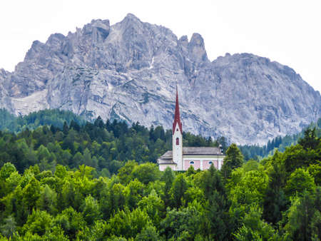 A church popping out of the forest, with a tall, sharp and rocky mountains behind. The church is build on a rock, making it taller than surrounding trees. Massive Alps in the back. Clear day.