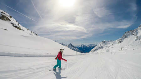 A snowboarder going down the slope in Moelltaler Gletscher, Austria. Perfectly groomed slopes. High mountains surrounding the girl wearing colourful snowboard outfit. Girl wears helm for the protection