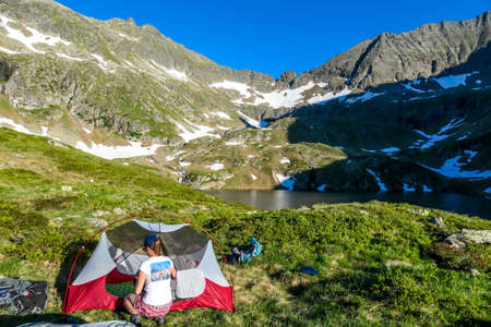 A woman camping in a wilderness. She sits next to a small tent, placed on a top of a mountain peak, waiting for the sunset. High mountains around. Spring in alpine valleys. Calmnes and happiness.