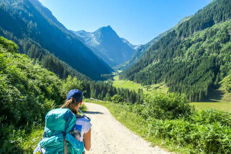 A young woman with a big hiking backpack walking on a wide pathway in a valley. Beauty of the nature. Lush green grass and trees overgrowing the meadow. Spring in the Alps.