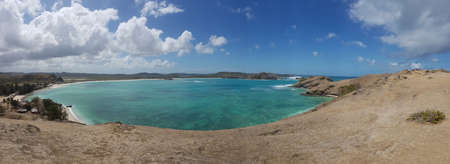 A panoramic view on an idyllic Pink Beach on Lombok, Indonesia. Sea is calm, shining with many shades of blue. Beauty in the nature. Unspoiled, hidden gem. Perfect place for peaceful, relaxed holidays Banco de Imagens
