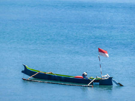A little blue boat drifting peacefully on a calm surface of the sea. The boat has an Indonesian flag attached to it. Pink beach, Lombok, Indonesia.