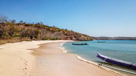 A peaceful Pink Beach in Lombok, Indonesia. Some boats are placed on the shore, others are drifting on a calm surface of the sea. Hidden gem of Indonesia, unspoiled place by humans. Relaxation