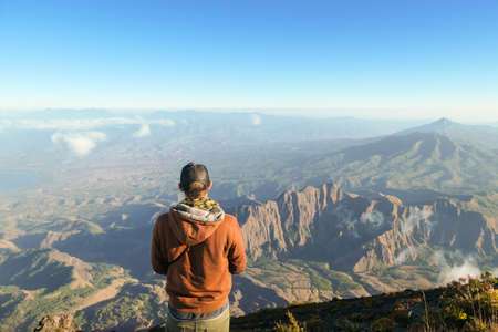 A man standing of the top of volcano Inerie in Bajawa, Flores, Indonesia. He is enjoying the beautiful view on volcanic island. He spreads her hands wide in a gesture of freedom. Clouds around him