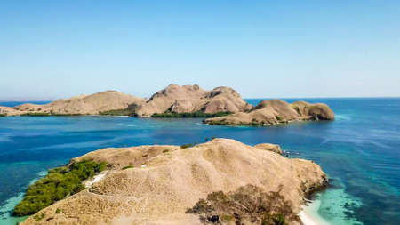 A drone shot of two bigger paradise islands in Komodo National Park, Flores, Indonesia. The islands have scarcely any trees and bushes. Dry land. Idyllic white sand beaches. Island hoping