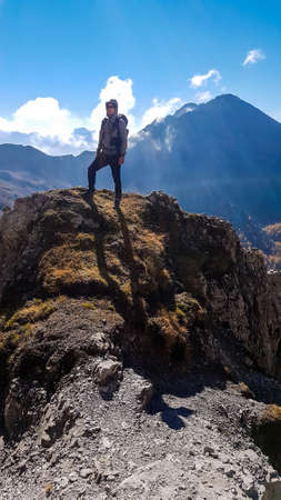Man with hiking backpack standing on the boulder, while walking to the Grosse Gamswiesenspitze, Lienz Dolomites, Austria. Solo wandering in Alps. Admiring beauty of the nature. Adventure and freedom