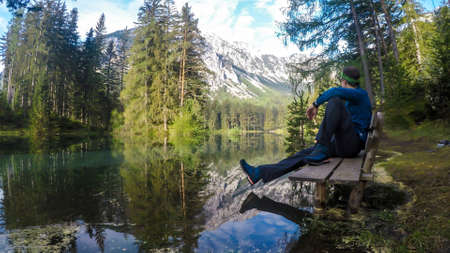 Man sitting on the bench, surrounded by the water of Green Lake in an Alpine valley in Austria and enjoying the mountain view. Spring in the valley. Dense forest in the back. Playtime and happiness.