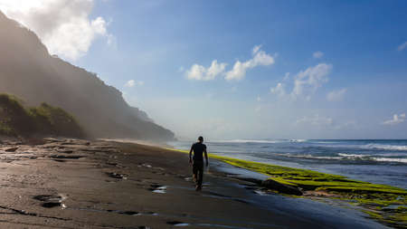 A man walking on a stony Nyang Nyang beach, covered with algae and seaweed, Bali, Indonesia. There are cliff on the side. Black lava beach. Discovering and exploring new places. Clear day.