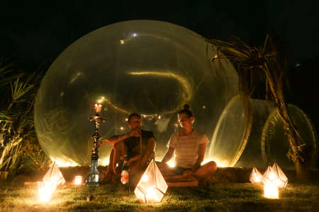 A couple sitting outside of a transparent bubble hotel, surrounded by candle light and smoking shisha, next to Nyang Nyang Beach, Bali, Indonesia. Luxury holiday. Romantic getaway. They are enjoying