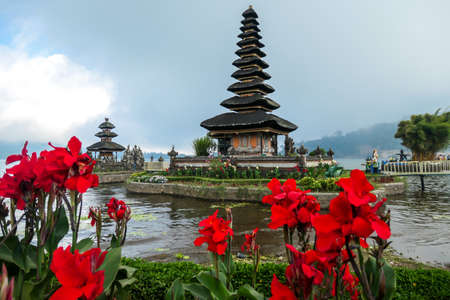 View on the front of main building of Ulun Danu Temple, Bali, Indonesia, through red flowers. Beautiful of Hindu water temple. Sacred place. Discovering new cultures. The temple is surrounded by water Foto de archivo