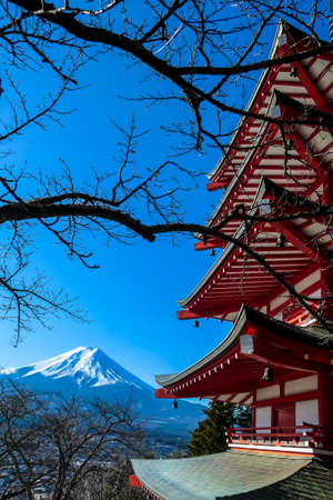 View on Chureito Pagoda and mountain of the mountains Mt Fuji, Japan captured on a clear, sunny day in winter. Top of the volcano covered with snow. Trees aren't blossoming yet. Postcard from Japan.