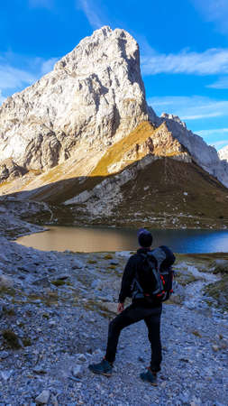 A man in hiking outfit enjoying the view on Wolayer Lake in Austrian Alps. There is massive, rocky mountain on the other side of the lake. New day beginning. Soft reflections in the lake. Happiness Archivio Fotografico