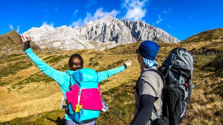 Couple in hiking outfits wandering in Italian Alps. Sharp slopes on both sides of the valley. Hard to reach mountain peaks. There are many mountain ranges in the back. Serenity and calmness. Freshness