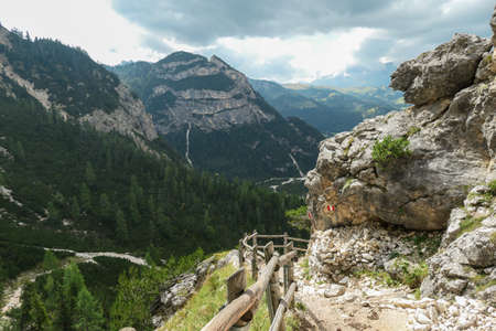 A panoramic view on the valley in high Italian Dolomites. There is a dense forest at the foothill, steep and sharp mountain chain in the back. A massive mountain slope on the side. A bit of overcast