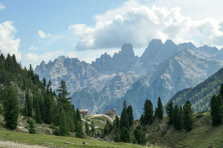 A panoramic view on the high Italian Dolomites, hiding under the clouds. Sunny day. There is a small cottage at the end of a small pathway. Lush green plateau around. Few trees growing in between