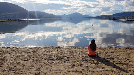 A woman in orange hoodie sitting at the sandy beach by the Woerthersee in Austria. The calm lake's surface is reflecting the surrounding mountains and clouds. Alpine landscape. The woman is meditating
