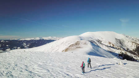 A drone shot of a couple wearing snow shoes hiking up to the peak of Speikkogel in Austrian Alps. The whole slope is covered with snow. many mountain chains in the back. Winter outdoor activity. Fun 스톡 콘텐츠