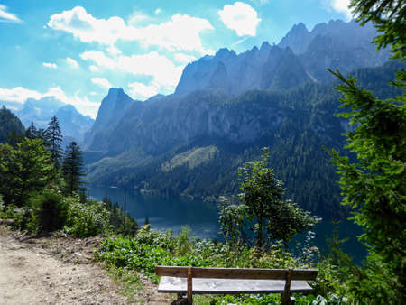 Gravelled road in the mountains with the view on high Alps in the region of Gosau, Austria. A wooden bench next to the road, with the wie on Gosau lake. Endless mountain chains. Serenity and calmness