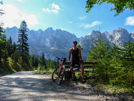 A man in biking outfit standing next to orange mountain bike next to a gravelled road in the mountains with the view on high Alps in the region of Gosau, Austria. Stony and barren mountain chains.