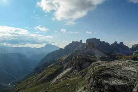A panoramic view on a vast valley in Italian Dolomites. The valley is surrounded with high mountains from each side. There are a few clouds above. Remote and isolated place. Remedy