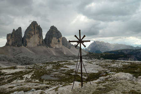 A metal cross with the view on the famous Tre Cime di Lavaredo (Drei Zinnen) in Italian Dolomites. The mountains are surrounded by thick clouds. Spirituality and achievement. Natural wonder.