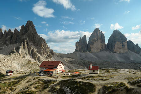 Drei Zinnenhuette and a small chapel, with red rooftop and small bell tower with the view on the Tre Cime (Drei Zinnen) in Italian Dolomites. There are high Alpine peaks around. Sunny day. Shelter
