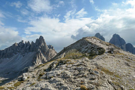 A panoramic view on Toblinger Knoten and surrounding mountains in Italian Dolomites. Difficult ad dangerous climbing route. Stony valley below. Few narrow pathways on the side. Freedom and serenity