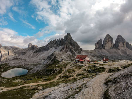 A capture of the Tre Cime di Lavaredo cottage (Drei Zinnenhuette) in Italian Dolomites with a turquoise lake behind. The cottage has red decorative elements. There are high Alpine peaks around. Shelter