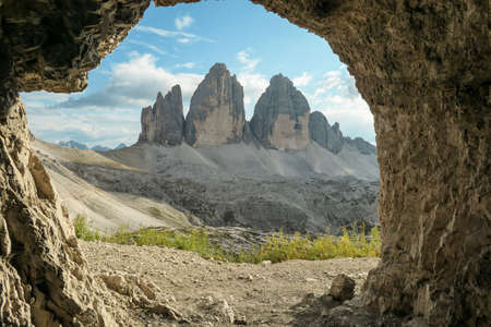 A view from inside a cave on the Tre Cime di Lavaredo (Drei Zinnen) in Italian Dolomites. Peaceful scenery. Steep and sharp mountain peaks. Sunny day. Sneak peaking. Serenity and meditation