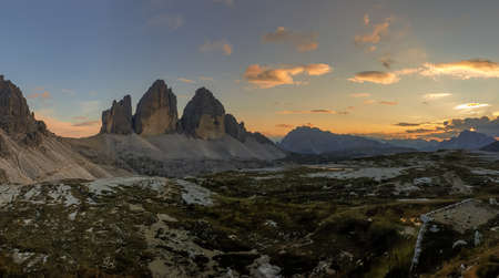 Golden hour over famous Tre Cime di Lavaredo (Drei Zinnen), mountains in Italian Dolomites. The mountains are surrounded with orange and pink clouds. Desolated and raw landscape. Sunset time. Serenity