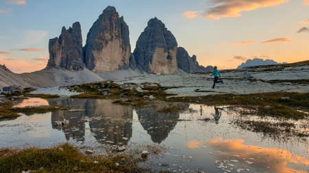 A woman enjoying the sunset over the Tre Cime di Lavaredo (Drei Zinnen) mountains in Italian Dolomites. The peaks reflect in a paddle. The mountains are surrounded with orange and pink clouds. Freedom