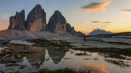 A man enjoying the sunset over the Tre Cime di Lavaredo (Drei Zinnen) mountains in Italian Dolomites. The peaks reflect in a paddle. The mountains are surrounded with orange and pink clouds. Freedom