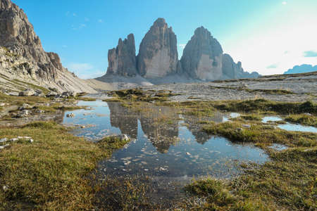 A panoramic view on the famous Tre Cime di Lavaredo (Drei Zinnen), mountains in Italian Dolomites. The mountains are reflecting in small paddle. Desolated and raw landscape. Natural phenomenon