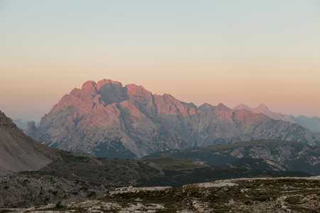 Golden hour in Italian Dolomites. The mountains are shining with pink and orange. Sunrise in high mountains. Morning haze. Lower parts of the valley still covered with shadow. New day beginning