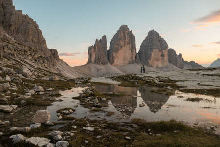 A couple enjoying the sunset over the Tre Cime di Lavaredo (Drei Zinnen) mountains in Italian Dolomites. The peaks reflect in a paddle. The mountains are surrounded with orange and pink clouds. Love