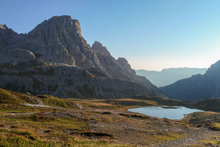 A panoramic view on a vast valley in Italian Dolomites during early morning hours. The valley is surrounded with high mountains from each side. Small lake in the middle. Remote and isolated place. 스톡 콘텐츠