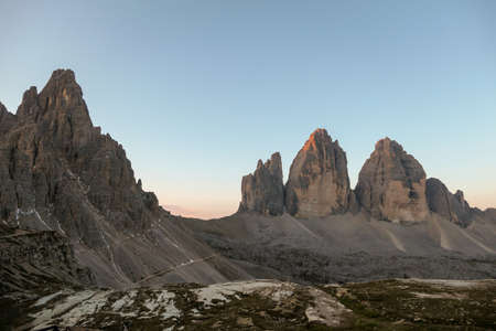A panoramic capture of the sunset above Tre Cime di Lavaredo (Drei Zinnen) and surrounding mountains in Italian Dolomites. The mountains are surrounded by pink and orange clouds. Golden hour. Serenity 스톡 콘텐츠