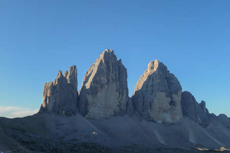 Golden hour in the Tre Cime di Lavaredo (Drei Zinnen) in Italian Dolomites. The mountains are reflecting golden sunrays. There is a lot of landslides and lose stones around. Natural wonder. Sunset