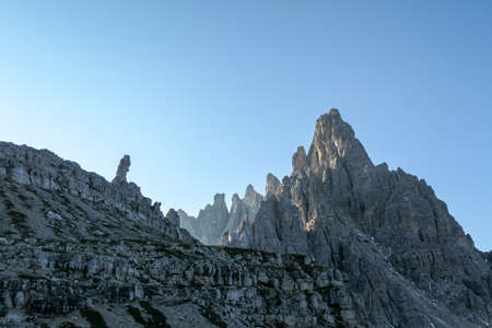 A capture of high and sharp peaks of Frankfurter Wuerstel in Dolomites, Italy during the early morning.  Lots of lose stones and pebbles. Raw and desolated landscape. Daybreak. Serenity and calmness. 스톡 콘텐츠