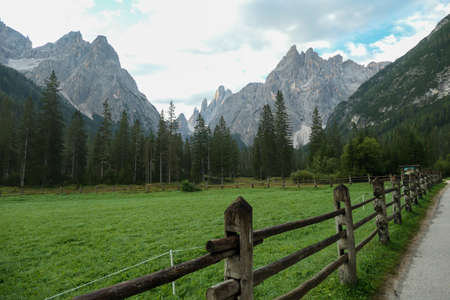 A gravelled road leading along a lush green meadow, secured with a wooden fence, leading to Italian Dolomites. Morning fog in the valley. Thick forest on the other side of the road. Idyllic landscape