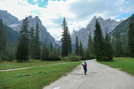 A woman with a big hiking backpack hiking in the Italian Dolomites. There are high and sharp mountain peaks in front of her. She walks on a wide, gravelled road surrounded by a few trees. Remedy 스톡 콘텐츠