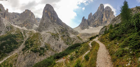 A narrow, stony pathway leading to high, Italian Dolomites. There are many high and sharp peak in front, with many landslides. Dangerous climbing. There are few trees on the side of the pathway.