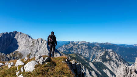 A man with a hiking backpack standing at the edge of a high mountain, Hohe Weichsel in Austria. The man in enjoying the calmness and peace. Lush green pasture around him. Exploration and discovery
