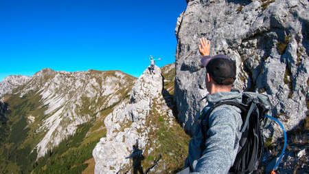 A woman with a hiking backpack standing on top of a big boulder on the way to Hohe Weichsel in Austria, with a panoramic view on a vast valley. The man is taking a selfie of them. Happiness and fun