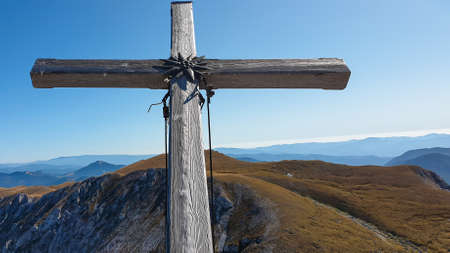 A wooden cross on top of Hohe Weichsel, Alpine peak in Austria. The cross is leaning, as if it was going to fall. There are endless mountain chains behind it. Early fall. The slopes are turning golden 스톡 콘텐츠