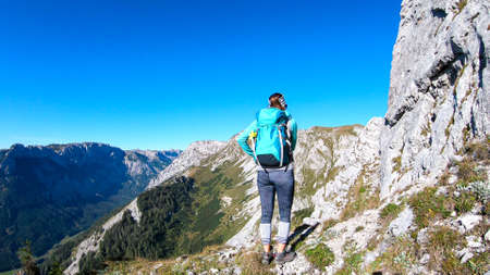 A woman with a hiking backpack climbing to the of a big boulder on the way to Hohe Weichsel in Austria, with a panoramic view on a vast valley.  Narrow pathway. She is enjoying the view. Discovering 스톡 콘텐츠
